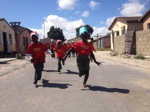 Zie hier de spelende kinderen in een township waar deze projecten plaatsvinden